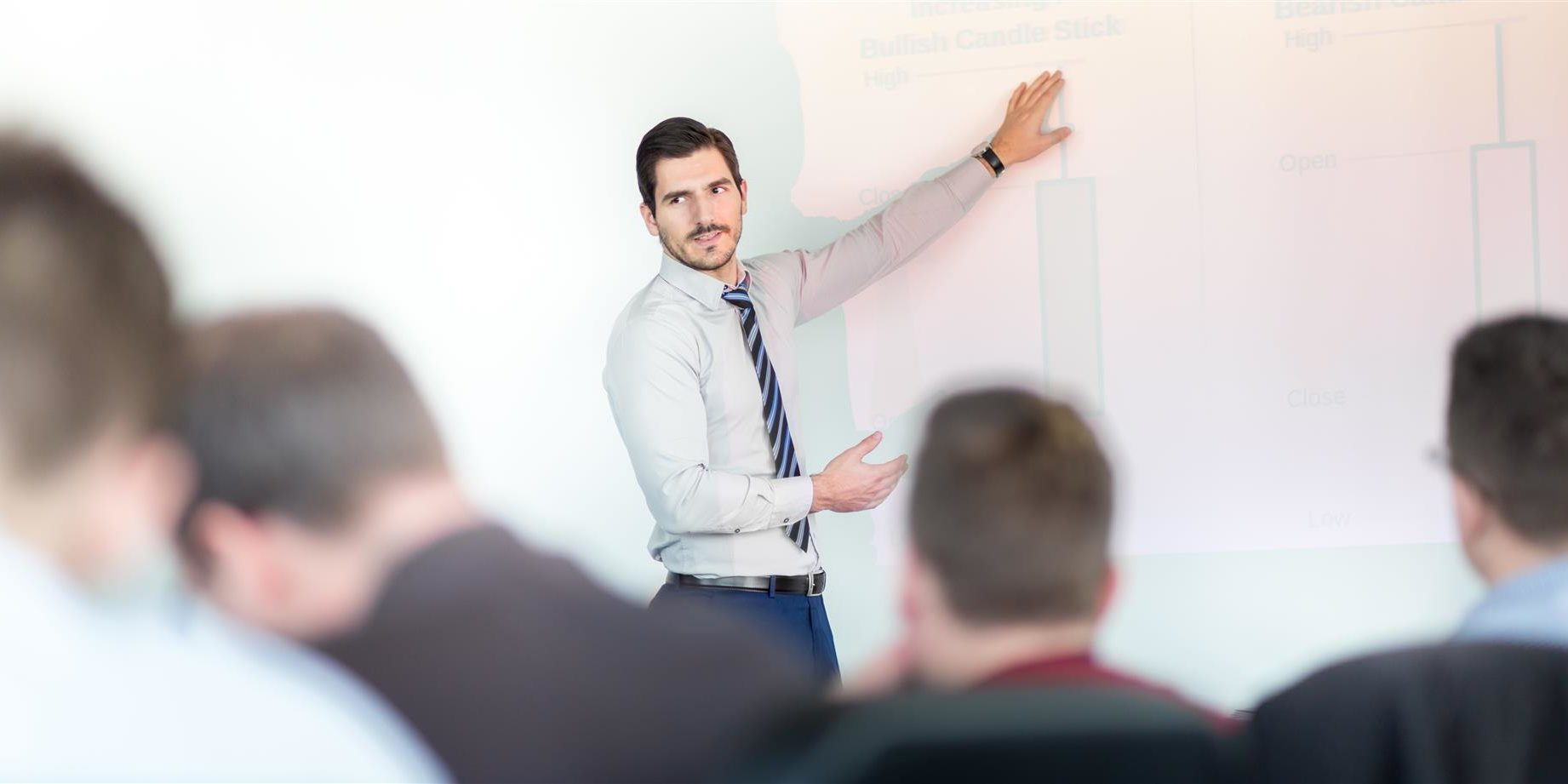 Man giving presentation in front of group of evaluators